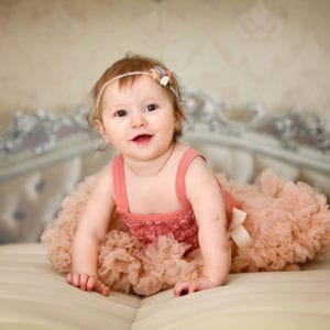 Baby girl photographed on a bed