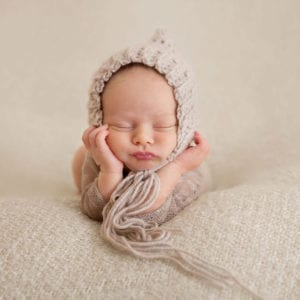Cute newborn baby in wooden bonnet