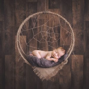 Photograph of newborn baby in dreamcatcher