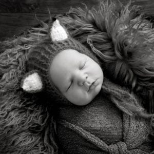 Black and white photo of newborn in cute fox outfit