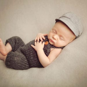 Cute newborn baby in woollen dungarees and engineer's cap