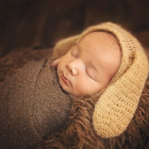 Photograph of sleeping newborn baby with rabbit ears